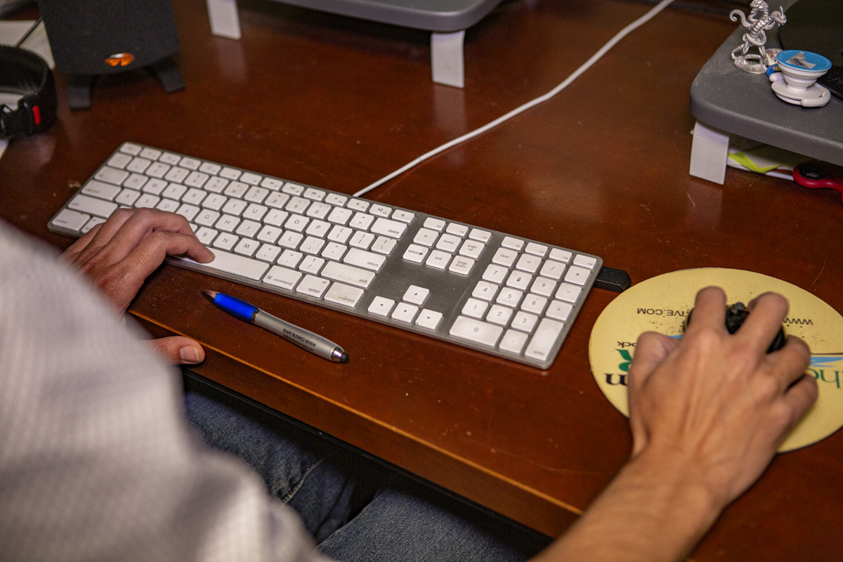 Person typing and clicking on computer